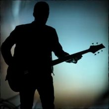 silhouette of a musician playing an F Bass instrument